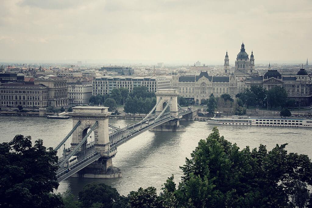 Výhľad na Budapešť v popredí s režazovým mostom cez Dunaj v pozadi s bailikou svätého Štefana