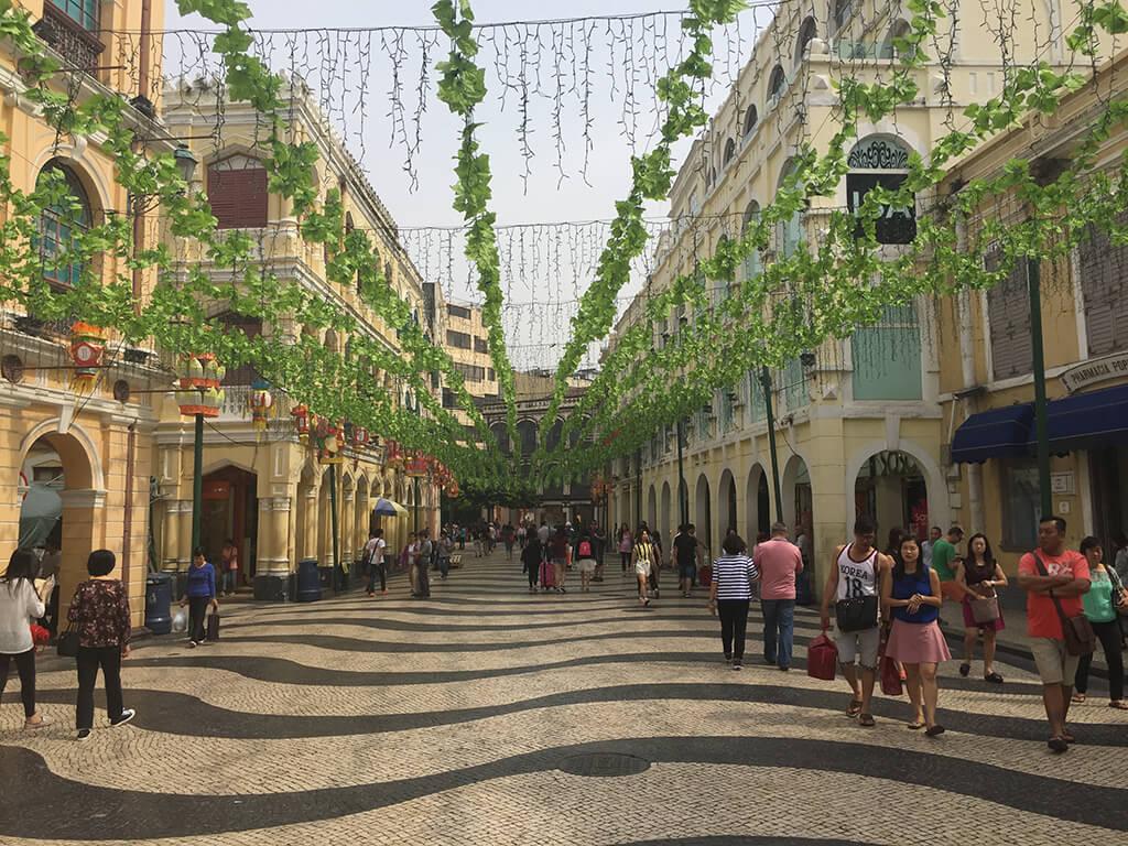 námestie s kockouvou dlažbou v tradičnej portugalskej architektúre ponad ktoré sa ťahajú zelené popínavé rastliny