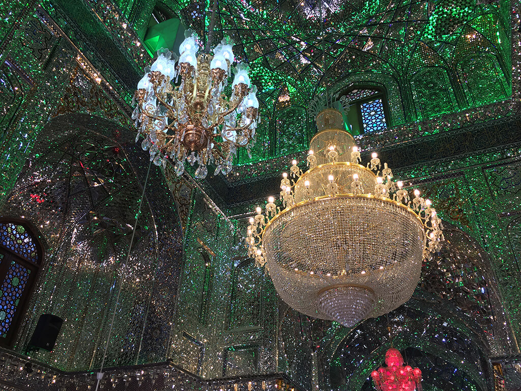 Nádherne zdobený trblietavý do zelena sfarbený interiér mešity s troma veľkými lustrami