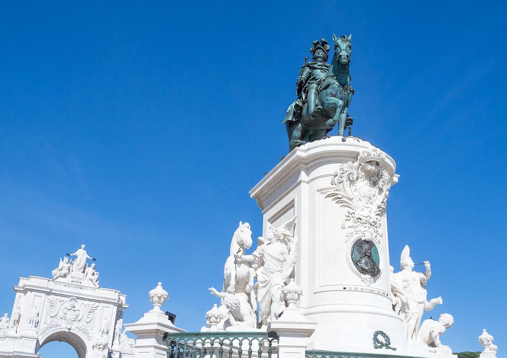Bronzová socha krála na koni postavena na veľkom bielom podstavci