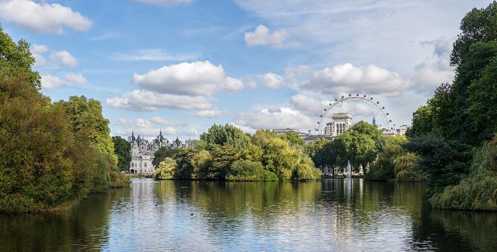 Pohľad na jazero v St.James parku v Londýne s množstvom zelene budovami a londýnskym okom v pozadí.