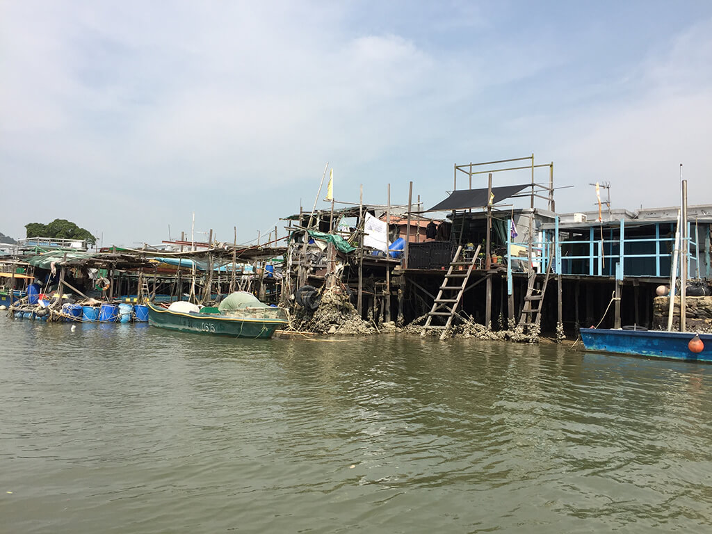 Tradičná rybárska osada s drevenými domami na koloch a množstvo bordelu naokolo