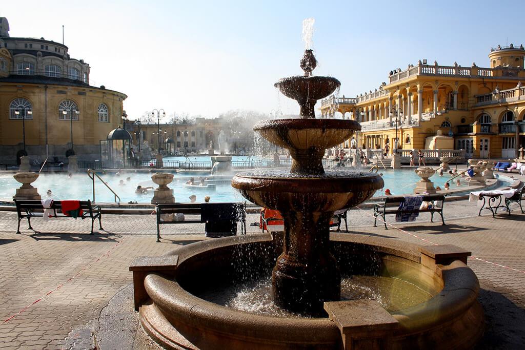 trojúrovňová fontána s bazénmi a kúpelným domom v pozadí.