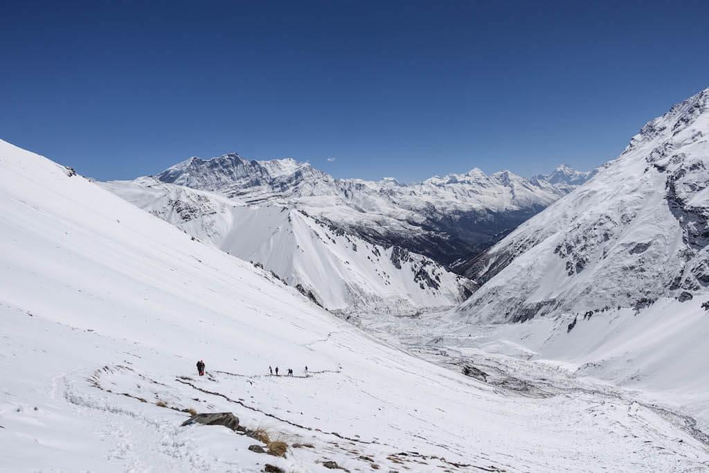 Výhľad počas výstupu k jazeru Tilicho do údolia Manangu obklopeného zasneženými himalájskymi štítmi
