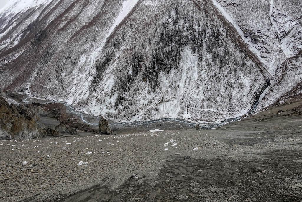 Pohľad z chodníka do hlbokého údolia v zóne zosuvov na ktoreho dne sa nachádza kľukatá rieka