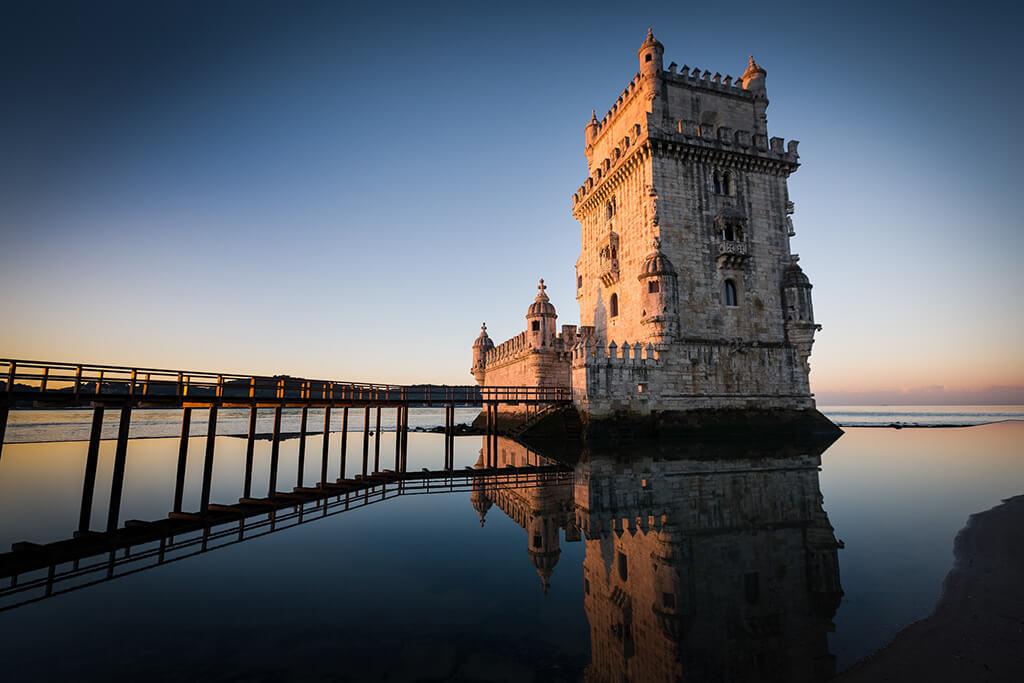 Historická veža zo 16. storočia na brechoch Lisabonu pri západe slnka, ktorá v minulsti tvorila súčasť obranného systému mesta.