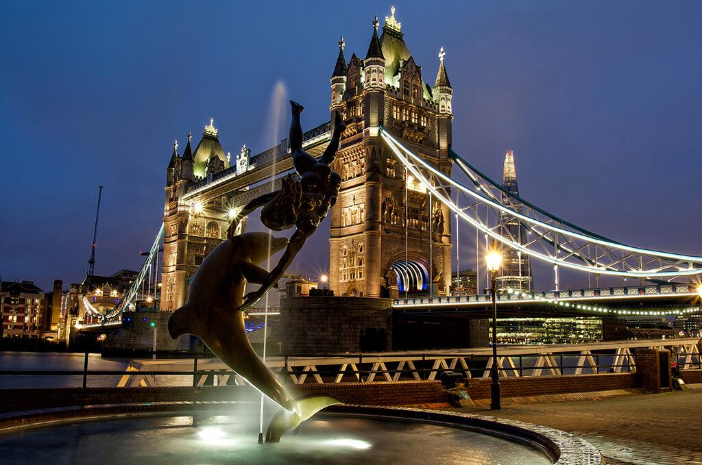 Nočný pohľad od fontány s dievčaťom a delfínom na vysvietený most Towerbridge v pozadí s najvyššou budovou EÚ The Sard prezývanú aj črep.