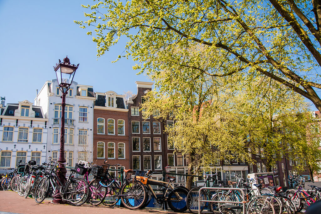 Ulica v Amsterdame plná bicyklou s lampou a historickymi domami v pozadi