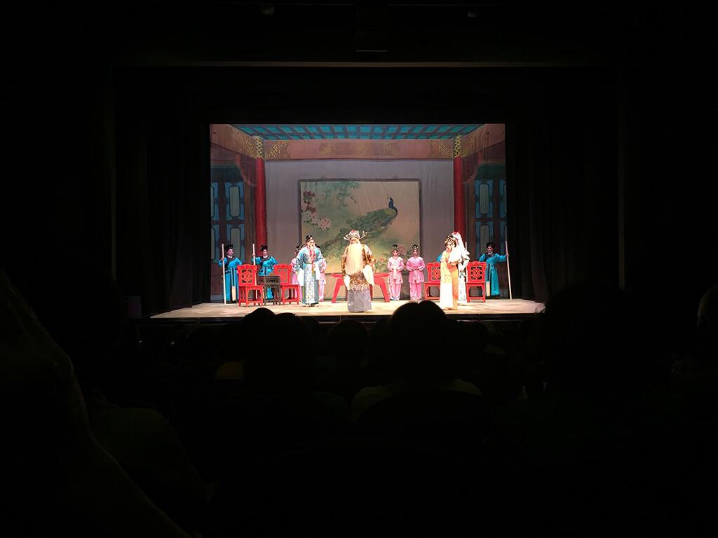 Pohľad v tme na javisko v divadle na hercov oblečených v tradičných čínskych krojoch